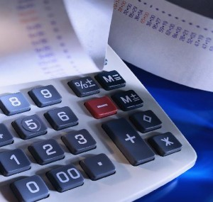Calculator with rolls of calculations from payroll showing the time and money paperless payroll can save